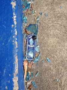 A Bombay Sapphire gin bottle smashed next to a blue curb
