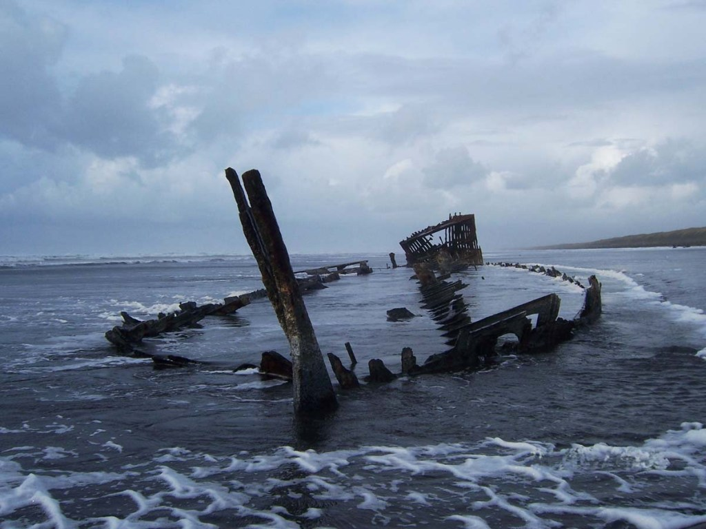 Remains of a metal sailing ship lying on an Oregon beach
