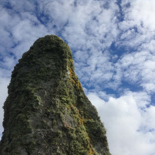 Moss-covered standing stone silhouetted against clouds and blue sky