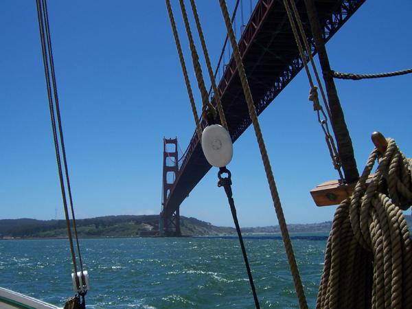 A Scow Schooner Sailing Under The Golden Gate Bridge